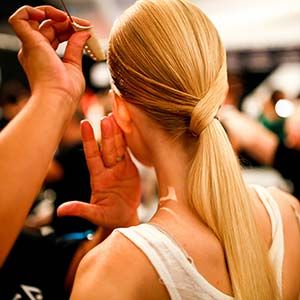 A model with long blonde hair getting ready for a fashion show