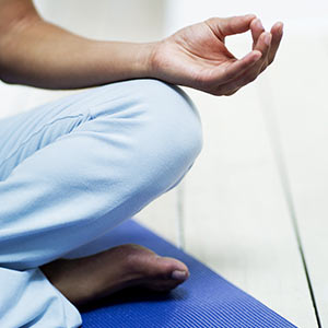 Young woman in a meditation pose on the floor