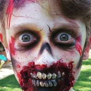 A child with face paint to look like a zombie